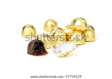Chocolate cherry candy in golden wrappers, one half eaten - stock photo