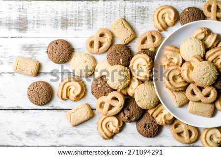 Chocolate chip and butter cookies with white ceramic dish on wood table
