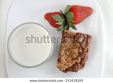 Chocolate chip cookie brownie with strawberries and glass of milk. - stock photo