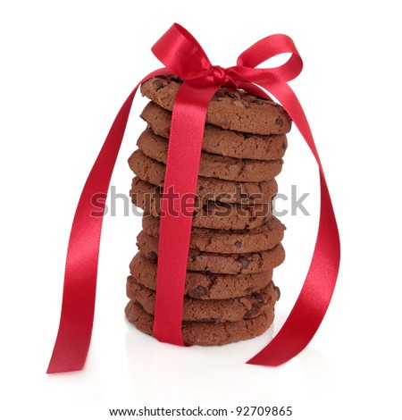 Chocolate chip cookie stack tied with a red satin ribbon isolated over white background.