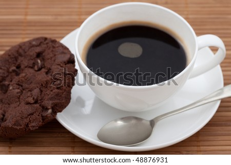 Chocolate chip cookie with a cup of black coffee in a white cup