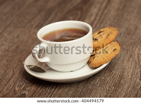 chocolate chip cookies and cup of tea on wooden table