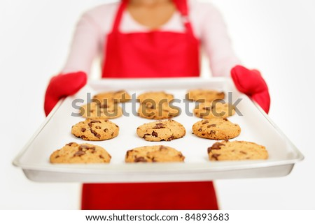 chocolate chip cookies - baking woman. Housewife showing tray with fresh baked cookies isolated on white background. Shallow depth of field.