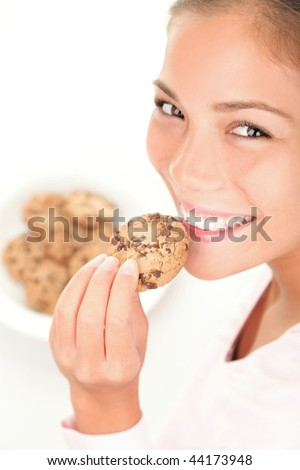 Chocolate chip cookies eating. Cute mixed race chinese / caucasian model on white background. - stock photo