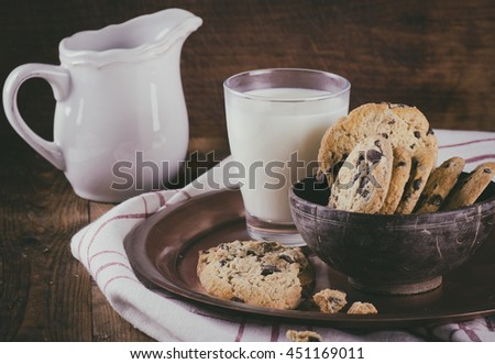 Chocolate chip cookies in a bowl on wooden table with glass of milk- retro style toned