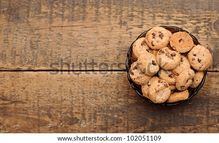 chocolate chip cookies in a cup on wooden table - stock photo