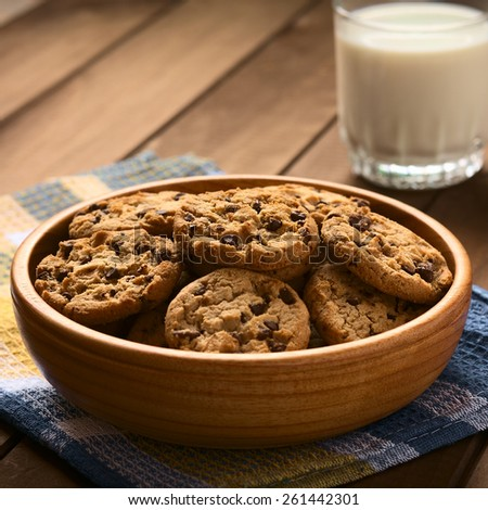 Chocolate chip cookies in wooden bowl with a glass of cold milk in the back, photographed on cloth on wood with natural light (Selective Focus, Focus in the middle of the cookies) - stock photo