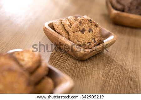 Chocolate chip cookies in wooden cup on table.