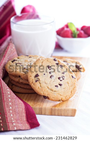 Chocolate chip cookies on a board with milk and fresh raspberries