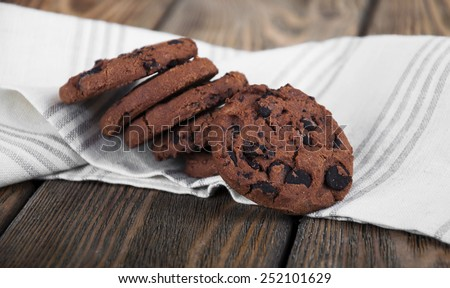 Chocolate chip cookies on linen napkin on wooden background - stock photo
