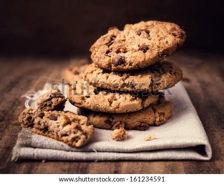 Chocolate chip cookies on linen napkin on wooden table. Stacked chocolate chip cookies close up. - stock photo