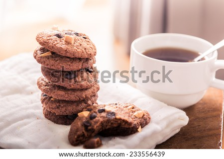 Chocolate chip cookies on napkin and hot tea on wooden table. Stacked chocolate chip cookies close up - stock photo