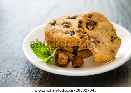 Chocolate chip cookies on white plate with mint and nuts, dark stone background - stock photo