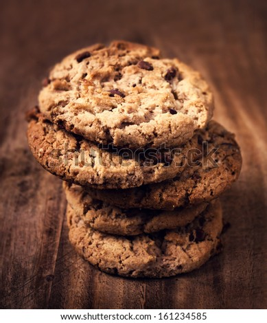 Chocolate chip cookies on wooden background. Stacked chocolate chip cookies shot with selective focus. - stock photo