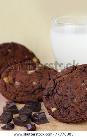 Chocolate chip cookies with a glass of milk and chocolate pieces on a beige background with a shallow DOF. - stock photo