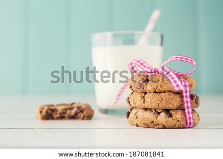 Chocolate chip cookies with a pink ribbon and a glass of milk with a straw on a white wooden table with a robin egg blue background. Vintage look. - stock photo