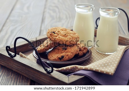 Chocolate chip cookies  with  milk in bottles on wooden tray - stock photo