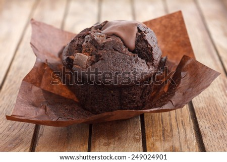 Chocolate chip muffin in brown wax paper. Unwrapped. - stock photo