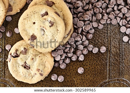 Chocolate chips cookies with loosely scattered chocolate chips over a rustic background. Perfect for the May 15th National Chocolate Chip Day! - stock photo
