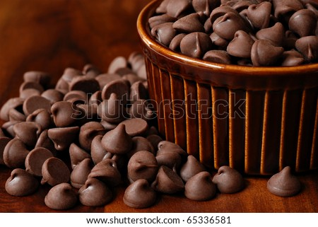 Chocolate chips overflowing from brown ceramic ramekin onto wood table.  Macro with shallow dof. - stock photo
