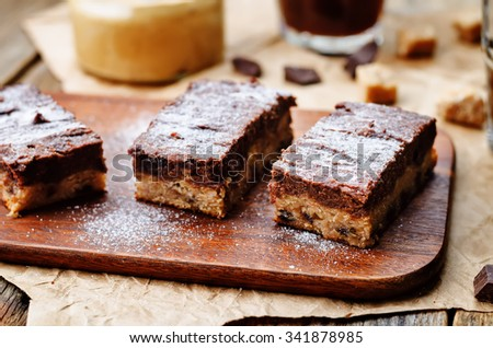 chocolate chips, peanut butter chocolate bars on a dark wood background. toning. selective Focus - stock photo