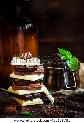 Chocolate / Chocolate bar / chocolate background/chocolate tower and glass with chocolate beans decorated with mint leaf. Dark  background. Selective focus. - stock photo