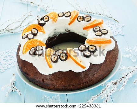 Chocolate Christmas cake with tangerines, hazelnuts in chocolate and whipped cream. Shallow dof. - stock photo