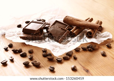 chocolate, cinamon and coffee beans on wooden table. selective focus. natural light.  - stock photo