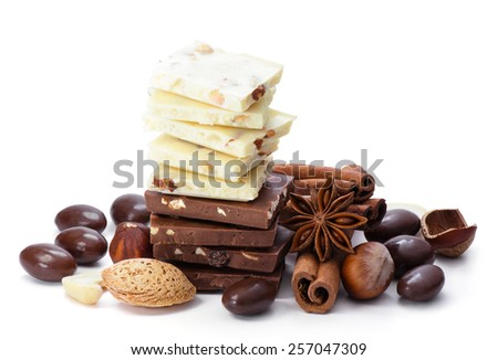 Chocolate, cinnamon and nuts isolated on white. - stock photo