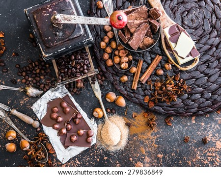 chocolate, cocoa and various spices on black table - stock photo