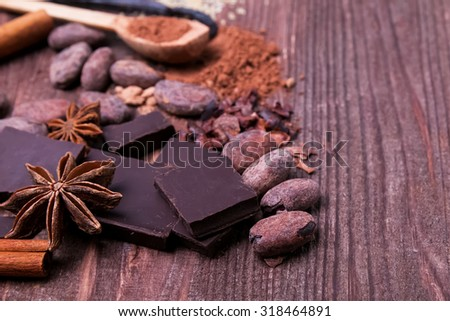 Chocolate, cocoa beans and spices on the wooden table, close-up - stock photo