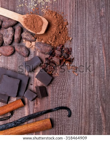 Chocolate, cocoa beans, cocoa powder and spices on wooden background, top view - stock photo