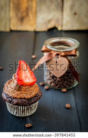 Chocolate coffee cupcakes muffins with strawberries on a plate with coffee beans. Wooden dark background - stock photo