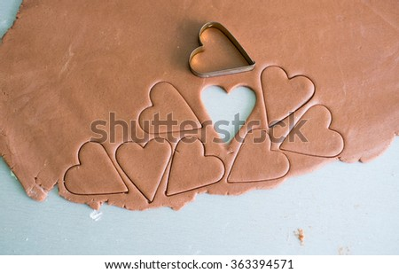 chocolate cookie dough is being cut to form cookies in shape of heart, chocolate cookie dough is on a grey kitchen table slightly covered with flour