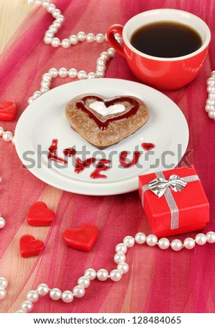 Chocolate cookie in form of heart with cup of coffee on pink tablecloth close-up