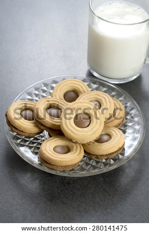 chocolate cookie with milk on  table, close up - stock photo