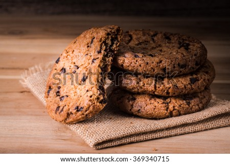 Chocolate cookies on brown linen napkin  on wooden table. Chocolate chip cookies shot on coffee colored cloth, closeup. - stock photo