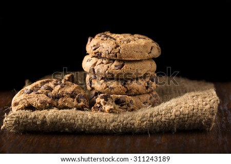 Chocolate cookies on white linen napkin on wooden table. Shot on coffee colored cloth - stock photo