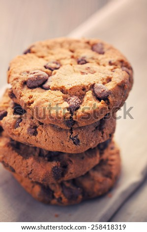 Chocolate cookies on white napkin on wooden background. Chocolate chip cookies shot on colored cloth, closeup. - stock photo