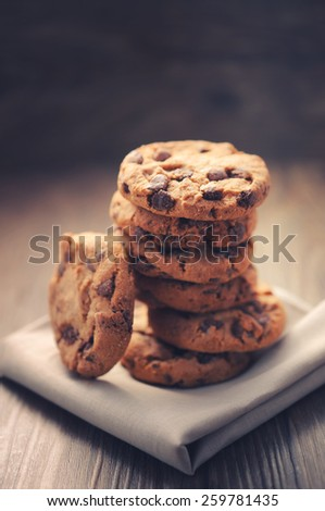 Chocolate cookies on white napkin on wooden background. Chocolate chip cookies shot on colored cloth, closeup.