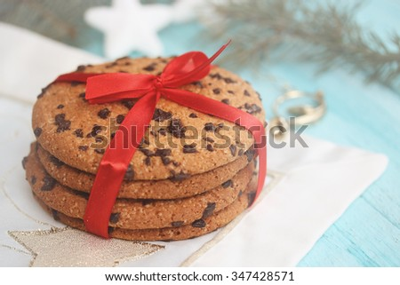 Chocolate cookies tied a red ribbon. Gift on a wooden background. Christmas background with copy space.  - stock photo