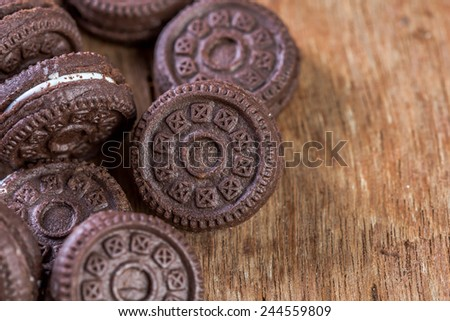 Chocolate cookies with creme on wooden table - stock photo
