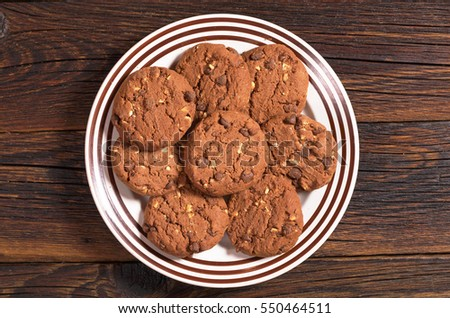 Chocolate cookies with nuts in plate on dark wooden table, top view