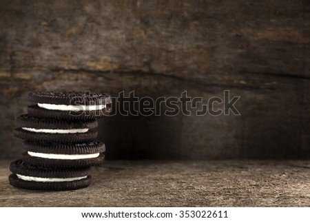 Chocolate cookies with white filling are on wooden table - stock photo