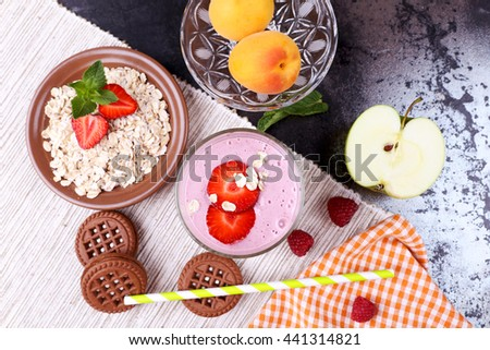 Chocolate cookies, yogurt smoothie with berries and cereal, strawberries, raspberries, half an apple and apricots on the table on the napkin. Milk-berry cocktail, straw, berries and cereals. - stock photo