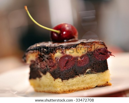 chocolate covered cake with cream and cherries - stock photo