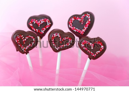 Chocolate covered cakepops shaped as hearts with pink sprinkles - stock photo