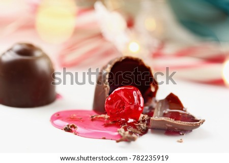 Chocolate covered cherries. Shallow depth of field with selective focus on bitten portion of candy truffle with exposed cherry.