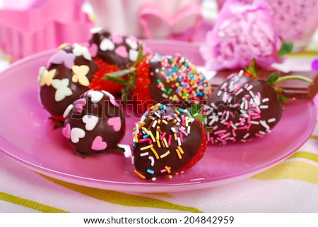 chocolate covered fresh strawberries with colorful sprinkles on pink plate for children  - stock photo