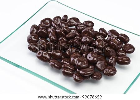 chocolate-covered raisins on transparent tray - stock photo